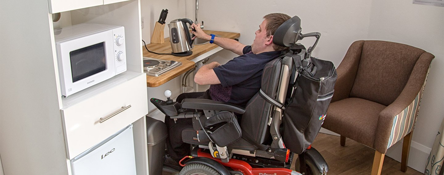 Disabled person filling a kettle