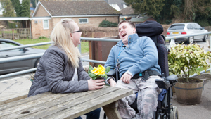Client laughing with carer at picnic bench
