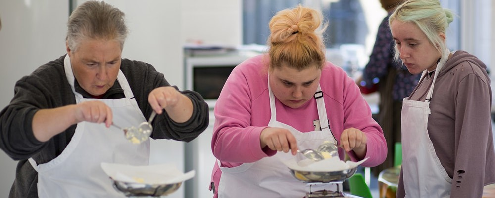 Clients measuring ingredients in the Training Kitchen